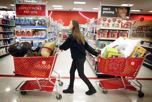 195964-a-woman-pulls-shopping-carts-through-the-aisle-of-a-target-store-on-th